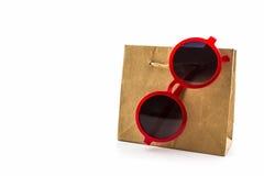 Gafas de sol rojas elegantes que cuelgan en el panier marrón Imagen de archivo