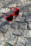 Gafas de sol rojas, en forma de corazón en un piso en una calle Imagen de archivo
