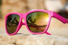 Gafas de sol rosadas elegantes en un embarcadero de madera con la reflexión de la playa imágenes de archivo libres de regalías