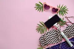 Gafas de sol rosadas elegantes, traje de baño moderno, teléfono en el palillo del selfie, Fotos de archivo libres de regalías