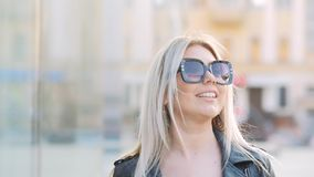 Gafas de sol rubias jovenes de la señora de la mujer emocionada metrajes