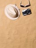 Gafas de sol, sombrero de mimbre y cámara Fondo de la arena Fotografía de archivo