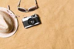 Gafas de sol, sombrero de mimbre y cámara Fondo de la arena Fotografía de archivo libre de regalías