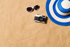 Gafas de sol, sombrero de mimbre y cámara Fondo de la arena Fotos de archivo libres de regalías