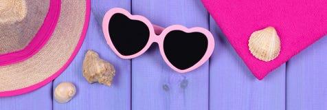 Gafas de sol, sombrero de paja y toalla en los tableros púrpuras, accesorios para el verano Fotos de archivo
