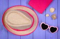 Gafas de sol, sombrero de paja y toalla en los tableros púrpuras, accesorios para el verano Fotos de archivo libres de regalías