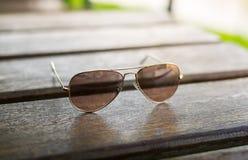 Gafas de sol tipo aviador en una tabla de madera fotografía de archivo libre de regalías