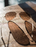 Gafas de sol tipo aviador en una tabla de madera Imagen de archivo