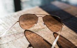Gafas de sol tipo aviador en una tabla de madera Fotos de archivo