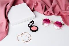 Gafas de sol y accesorios decorativos de los cosméticos sobre el fondo blanco Fotos de archivo libres de regalías
