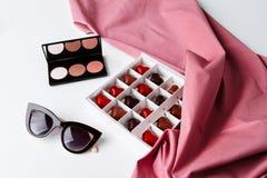 Gafas de sol y chocolate decorativos de los cosméticos sobre el fondo blanco Fotos de archivo