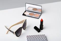 Gafas de sol y cuaderno decorativos de los cosméticos en la tabla blanca Foto de archivo