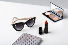Gafas de sol y cuaderno decorativos de los cosméticos en la tabla blanca Fotografía de archivo