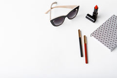 Gafas de sol y cuaderno decorativos de los cosméticos sobre el fondo blanco Imagen de archivo libre de regalías