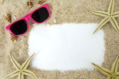 Gafas de sol y estrellas de mar en marco de la arena imagen de archivo libre de regalías