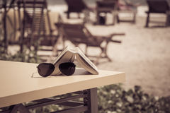 Gafas de sol y libro que mienten en una tabla en un café tropical de la playa Fotos de archivo libres de regalías