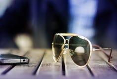 Gafas de sol y teléfono celular en la tabla Fotografía de archivo libre de regalías