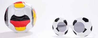 Gafas del deporte del fútbol y balón de fútbol con la bandera alemana Fotografía de archivo