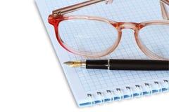Gafas en el cuaderno espiral Imagen de archivo libre de regalías