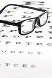Gafas en una carta de prueba del ojo Imágenes de archivo libres de regalías