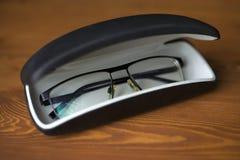 Gafas para mejorar vista en un caso en un fondo de madera oscuro fotografía de archivo libre de regalías