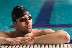 Gafas que llevan del nadador de sexo masculino y reclinación del casquillo de natación fotografía de archivo libre de regalías