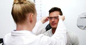 Gafas que prescriben del optometrista de sexo femenino al paciente metrajes