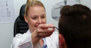 Gafas que prescriben del optometrista de sexo femenino al paciente almacen de metraje de vídeo