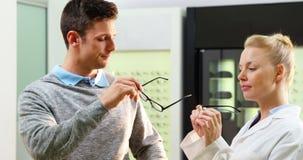Gafas que prescriben del optometrista de sexo femenino al paciente almacen de video