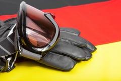 Gafas y guantes del deporte de invierno sobre bandera alemana Imagenes de archivo