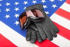 Gafas y guantes del deporte de invierno sobre bandera de los E.E.U.U. Foto de archivo