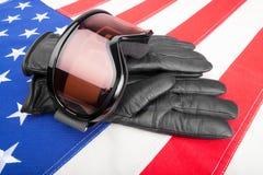 Gafas y guantes del deporte de invierno sobre la bandera de los E.E.U.U. - tiro del estudio Foto de archivo