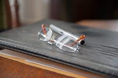 Gafas y lápiz en expediente fotografía de archivo