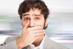 Gaffe: young man with his hand on his mouth Royalty Free Stock Image