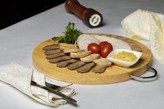 Gaffel och kniv i servett, blandat kött, ostsås och körsbärsröda tomater med lökcirklar på textilen royaltyfria foton