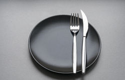 Gaffel och kniv på en svart platta Royaltyfri Bild