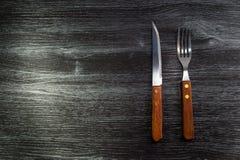 Gaffel och kniv på Wood texturbakgrund Arkivfoto