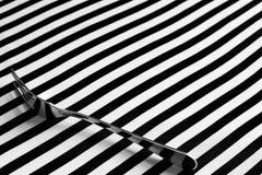 Gaffel på svartvit randig bakgrund royaltyfri foto