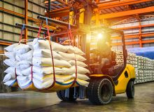 Gaffeltruck som behandlar sockerpåsen för att stoppa in i behållaren för export arkivbild