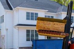 Gaffeltruck som laddar byggnadsmaterial En bunt av brädeträram och strålkonstruktionslogistik i materiel royaltyfria foton