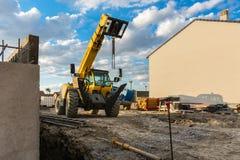 Gaffeltruckar i konstruktionen av ettfamilj hus fotografering för bildbyråer