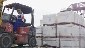 Gaffeltruckchaufför i en fabrik eller ett lager som kör mellan rader av att bordlägga med buntar av askar och att förpacka lager videofilmer