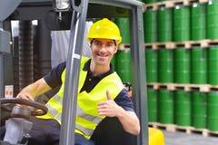 Gaffeltruckchaufför i en logistikkorridor av ett kemiskt lager royaltyfri bild