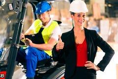 Gaffeltruckchaufför och arbetsledare på lagret Arkivbilder