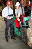 Gaffeltruckchaufför och arbetsledare på lagret Fotografering för Bildbyråer