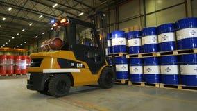 Gaffeltrucken tar och transporterar paletter med logotrummor från arbetare