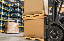 Gaffeltruckkartonger i ett lager warehouse den automatiska delen Arkivbild