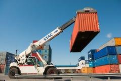 Gaffeltrucklyftande lastbehållare i sändande gård eller skeppsdockagård mot soluppgånghimmel royaltyfria foton
