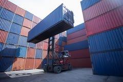 Gaffeltrucklyftande lastbehållare i sändande gård eller skeppsdockagård mot soluppgånghimmel för trans.import fotografering för bildbyråer