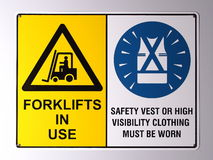 Gaffeltruckvarning och den höga synlighetsvästväggen undertecknar Arkivbilder